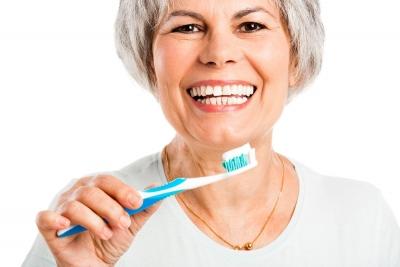 mujer sonriente por su revision periodica bucal e higiene profesional