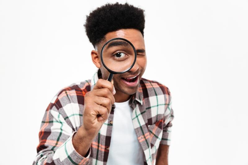 hombre con lupa buscando mitos de la odontologia